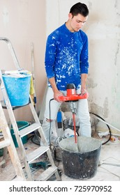 Worker mixing dry mortar with handheld mixer in bucket