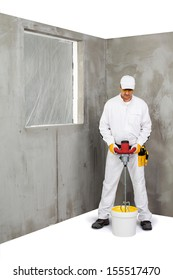 Worker mixing a plaster with a stirrer machine
