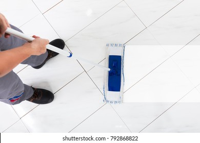 Worker Mopping Floor With Mop In Kitchen