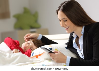 Worker mother working on line holding a smart phone while her toddler sleeps in a bed in her bedroom at home