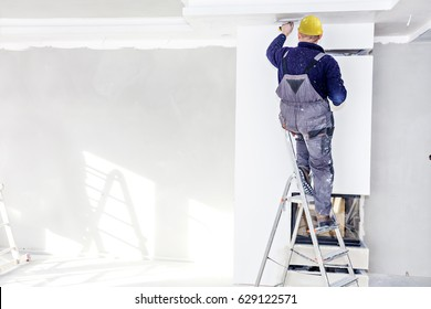 Worker mount suspended ceilings from plasterboard
