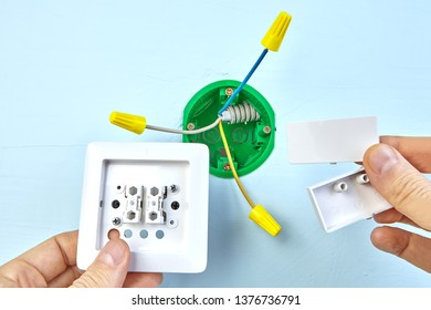 Worker is mounting european two-button switch, electrical installation.