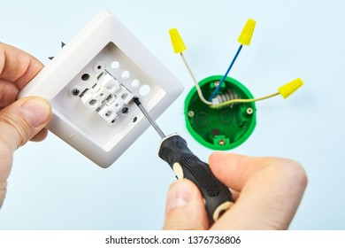 Worker is mounting new two-button switch with help of hand tool.