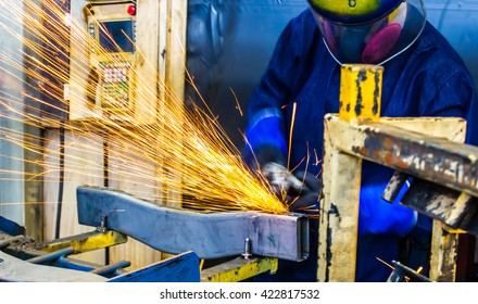 worker movement grinding metal in car manufacturing plant