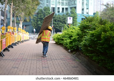 Worker moving a large piece of Wood to cover the road.