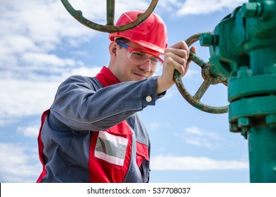 Worker near wellhead valve wearing red helmet in the oilfield. Oil and gas concept.