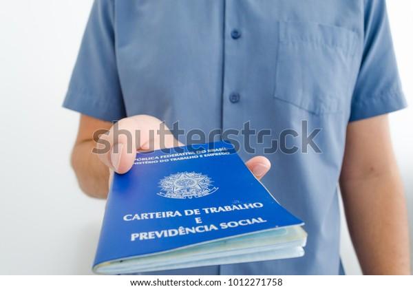 A worker with a new job show his work permit document from Brazil (Portuguese: trabalhador com novo emprego mostra sua carteira de trabalho, reforma trabalhista e previdência).