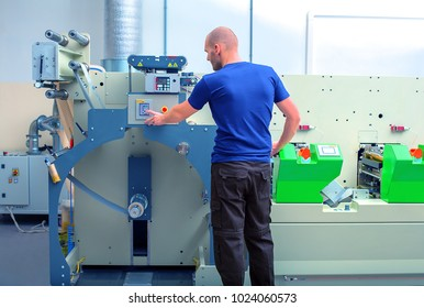 Worker next to the printing machine inputs the data by pressing the touch screen. Skilled printing operator controls printing machine via the touch screen. Rotary printing press. In-line press machine