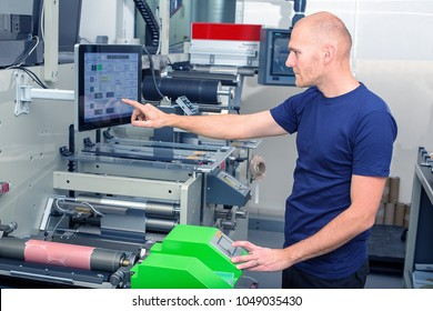 Worker next to the printing machine inputs the data by pressing the touch screen. Skilled printing operator controls printing machine via touch screen. Rotary printing press. In-line press machine.