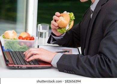 Worker in office eating healthy sandwich at his desk