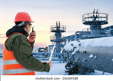 Worker at the oil field , natural gas storage in the background.Refinery , oil and natural gas