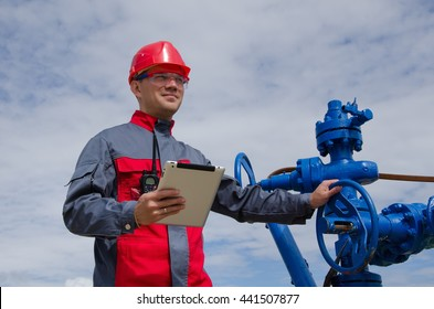 Worker in the oilfield near wellhead valve holding tablet computer and wearing red helmet. Oil and gas concept.