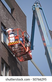 Worker on aerial access platform painting window frame