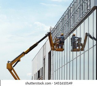 Worker on a aerial platform with their reflection on the glass facade under construction