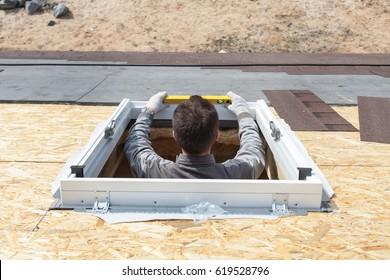 Worker on a asphalt shingle roof installing new plastic (mansard) or skylight  window