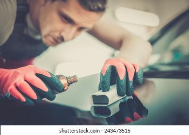 Worker on a car wash applying nano coating on a bonnet
