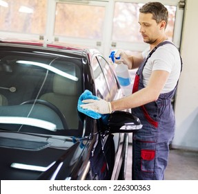 Worker on a car wash cleaning car with a spray