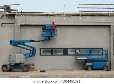 A worker on a cherry picker finishes the newly constructed facade of a new building. On the right an aerial platform