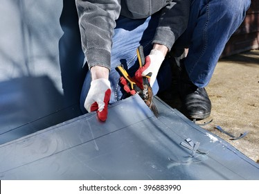 Worker on a construction site cut stainless steel sheet shears of metal cutting