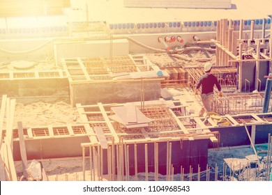 Worker on construction site. Industrial concept. Toned image with sunflare.
