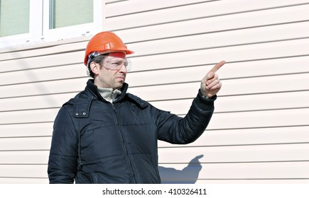Worker on a construction site in winter gives instructions gestures