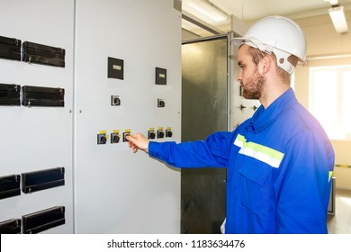 Worker on the control panel of industrial equipment. Automation of production. Electric engineer in the closet of protection and automation. Operation of electrical installation.