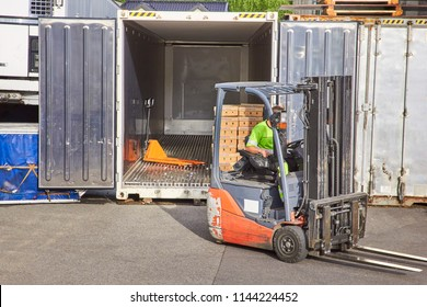 Worker on forklift loading car