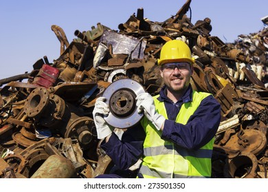 Worker on junkyard hold rotor like shiny trophy. Copy space available.
