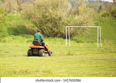 Worker on a large green lawn mower mows the grass on the football field. Landscape design and maintenance of green areas of the sports complex. Making grass stadium before the match. Human labor.