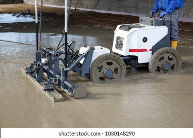Worker on a laser screed machine leveling fresh poured concrete surface on a construction site