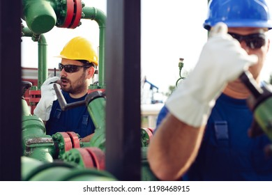Worker on oil pump looks at laptop and speaking in a radio station