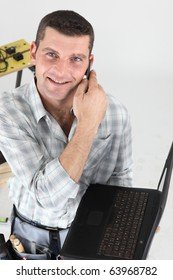 Worker on phone in front of laptop computer