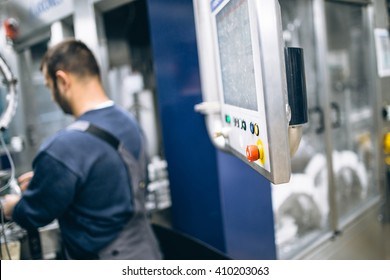 Worker on robotic line for bottling pure spring water. Selective focus on red button and short depth of field.