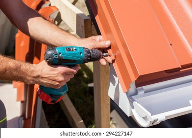Worker on a roof with electric drill installing red metal tile on wooden house