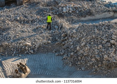The worker on the rubble pile on the construction site.