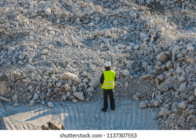 The worker on the rubble pile on the demolition site
