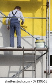 worker on a scaffold painting house with roller