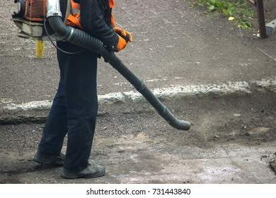 Worker on a street in autumn collects leaves and dust with a leaf blower