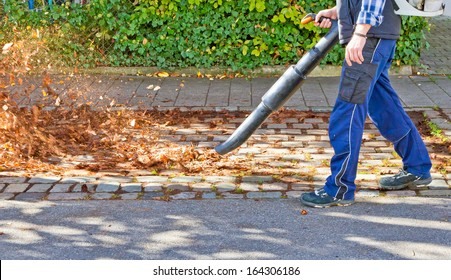 Worker on a street in autumn with a leaf blower