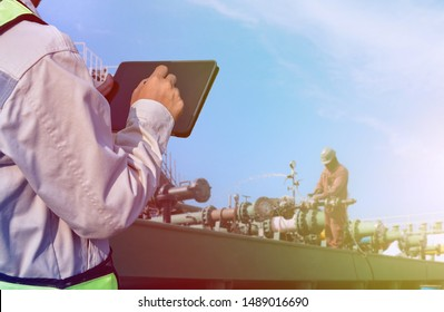 worker on tanker ship and holding tablet computer, Oil And Gas Industry. Work on the gas tanker safety monitor. industrial during pressure testing manifold pipe system on board in shipyard.