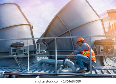 worker open valve of cooling tower on blue sky background.worker opening butterfly valve on top of cooling Tower. engineer check valve on cooling tower.