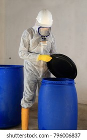 A Worker opening barrel with chemicalToxic waste Dangerous goods