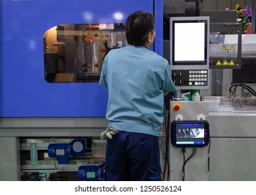 worker operate industrial plastic injection molding press machine for manufacturing