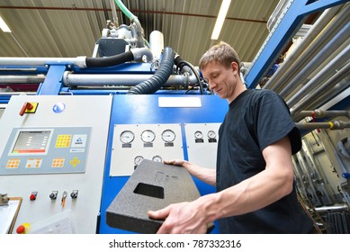 worker operates machine in the plastics industry - production of styrofoam components