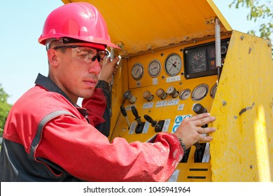 Worker Operating Drilling Rig Control Panel. Oil and gas well drilling worker operates drilling rig machinery. Selective focus.