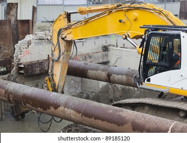 Worker operating excavator equipped with demolition hammer during the destruction of a reinforced concrete wall