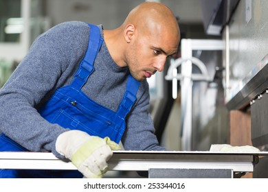 Worker operating a machine for bending sheet metal