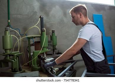 Worker operating welding machine in factory. PVC window and door welding machine.