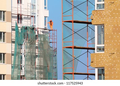 Worker in orange clothes stands on scaffolding of high-rise buildings under construction at sunny day.