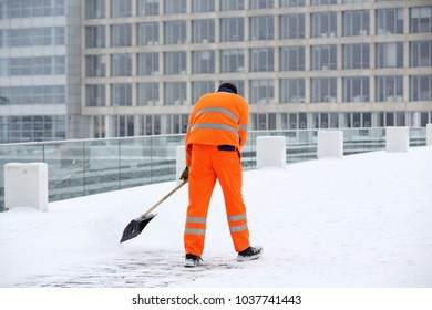 worker in orange outfit doing winter service snow removal in Dusseldorf